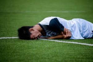 Man in acute pain playing soccer